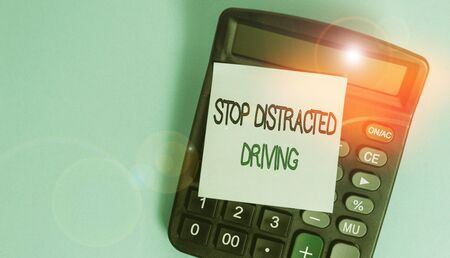 Text sign showing Stop Distracted Driving. Business photo showcasing asking to be careful behind wheel drive slowly Portable electronic calculator device blank sticky note colored background Stock Photo