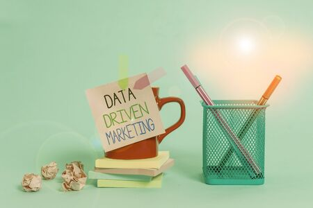 Word writing text Data Driven Marketing. Business photo showcasing Strategy built on Insights Analysis from interactions Cup pens holder note banners stacked pads paper balls pastel background