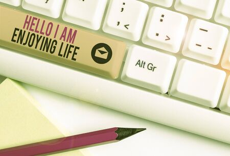 Handwriting text Hello I Am Enjoying Life. Conceptual photo Happy relaxed lifestyle Enjoy simple things White pc keyboard with empty note paper above white background key copy space