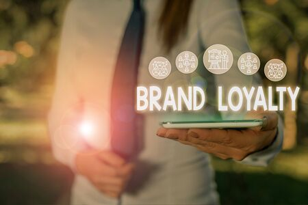 Conceptual hand writing showing Brand Loyalty. Concept meaning Repeat Purchase Ambassador Patronage Favorite Trusted Woman wear work suit presenting presentation smart device Imagens
