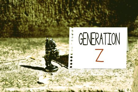 Word writing text Generation Z. Business photo showcasing name for the generation of children after the millennials Bronze Knight Chessman Blank Spiral Notepad Sheet Folded in Half Dry Leaves