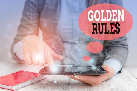 Text sign showing Golden Rules. Business photo text basic principle that should always follow to ensure success Female human wear formal work suit presenting presentation use smart device
