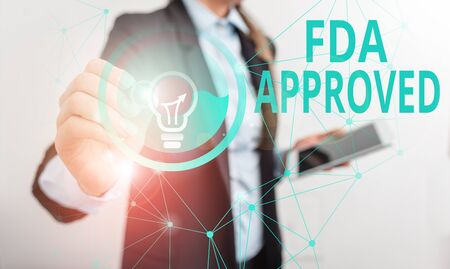 Conceptual hand writing showing Fda Approved. Concept meaning FDA agreed the product or formula is safe and or effective Male human wear formal suit presenting using smart device