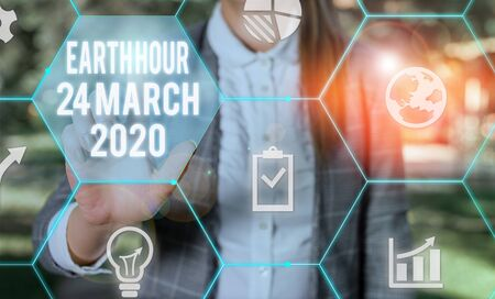 Writing note showing Earth Hour 24 March 2020. Business concept for Celebrate Sustainability Save the Planet Lights Off Female human wear formal work suit presenting smart device