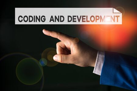 Writing note showing Coding And Development. Business concept for Programming Building simple assembly Programs Isolated hand pointing with finger. Business concept pointing finger