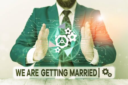 Text sign showing We Are Getting Married. Business photo showcasing Engagement Wedding preparation Loving couple Male human wear formal work suit presenting presentation using smart device
