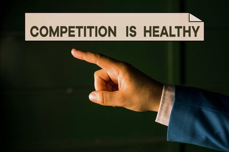 Writing note showing Competition Is Healthy. Business concept for Rivalry is good in any Venture leads to Improvement Isolated hand pointing with finger. Business concept pointing finger