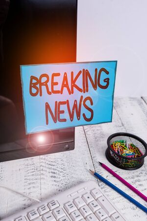 Conceptual hand writing showing Breaking News. Concept meaning Special Report Announcement Happening Current Issue Flashnews Note paper taped to black screen near keyboard stationary