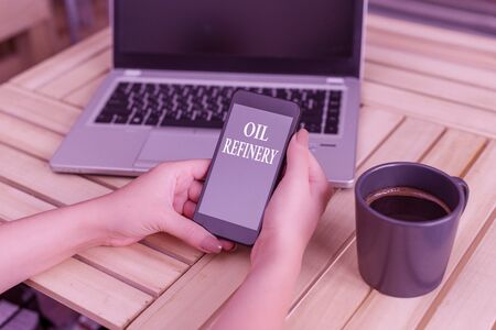 Writing note showing Oil Refinery. Business concept for industrial process of converting crude oil into petroleum woman with laptop smartphone and office supplies technology