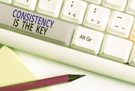 Text sign showing Consistency Is The Key. Business photo showcasing full Dedication to a Task a habit forming process White pc keyboard with empty note paper above white background key copy space