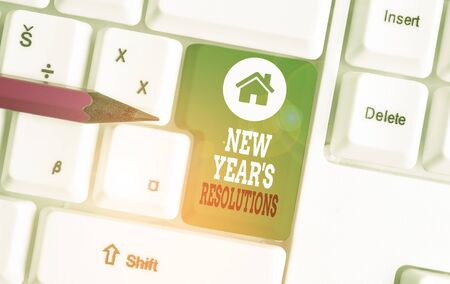 Text sign showing New Year S Resolutions. Business photo showcasing Wishlist List of things to accomplish or improve White pc keyboard with empty note paper above white background key copy space Stock fotó