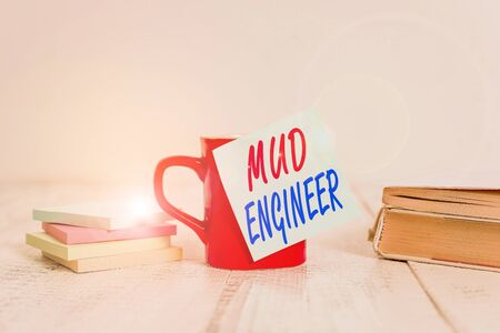 Text sign showing Mud Engineer. Business photo text liable for making mixture of fluids used in drilling process Coffee cup blank sticky note stacked note pads books retro old wooden table