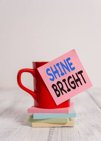 Handwriting text Shine Bright. Conceptual photo make an effort to live normally when in a difficult situation Coffee cup blank sticky note stacked note pads retro retro wooden table