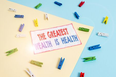 Conceptual hand writing showing The Greatest Wealth Is Health. Concept meaning being in good health is the prize Take care Colored clothespin paper reminder with yellow blue background