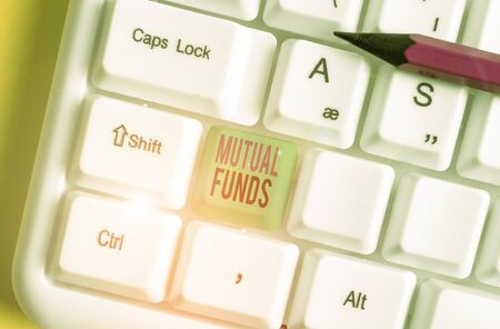 Text sign showing Mutual Funds. Business photo showcasing collection of stocks bonds or other securities from investors White pc keyboard with empty note paper above white background key copy space Stock Photo