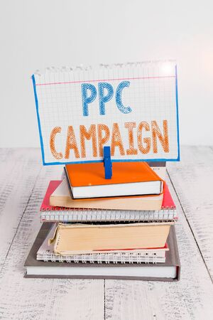 Text sign showing Ppc Campaign. Business photo text use PPC in order to promote their products and services pile stacked books notebook pin clothespin colored reminder white wooden