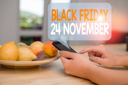 Word writing text Black Friday 24 November. Business photo showcasing Special sales Thanksgiving discounts Clearance woman using smartphone office supplies technological devices inside home