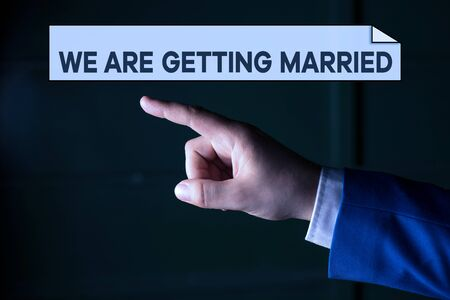 Writing note showing We Are Getting Married. Business concept for Engagement Wedding preparation Loving couple Isolated hand pointing with finger. Business concept pointing finger