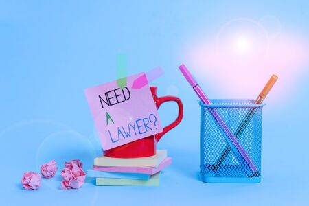 Word writing text Need A Lawyer Question. Business photo showcasing Legal problem Looking for help from an attorney Cup pens holder note banners stacked pads paper balls pastel background