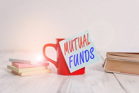 Text sign showing Mutual Funds. Business photo text collection of stocks bonds or other securities from investors Coffee cup blank sticky note stacked note pads books retro old wooden table