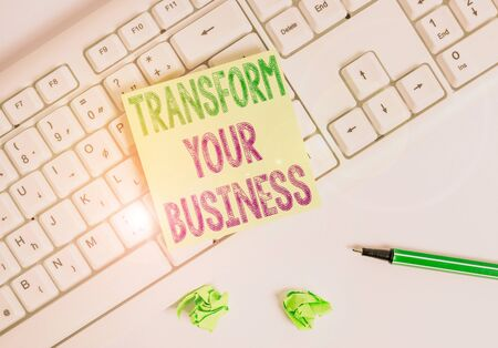 Writing note showing Transform Your Business. Business concept for Modify energy on innovation and sustainable growth Green note paper with pencil on white background and pc keyboard Stok Fotoğraf