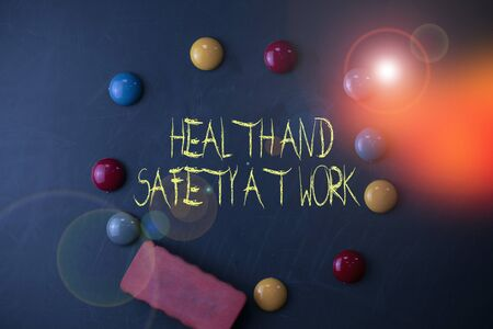 Word writing text Health And Safety At Work. Business photo showcasing Secure procedures prevent accidents avoid danger Round Flat shape stones with one eraser stick to old chalk black board Stockfoto