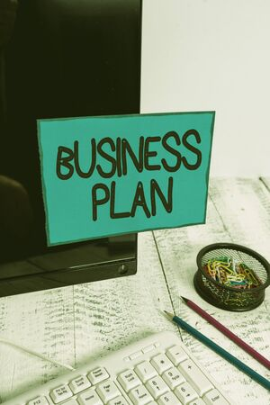Conceptual hand writing showing Business Plan. Concept meaning Structural Strategy Goals and Objectives Financial Projections Note paper taped to black screen near keyboard stationary