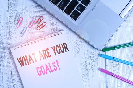 Handwriting text What Are Your Goals Question. Conceptual photo ask the Desired End Results to know the plans Slim metallic laptop blank spiral notepad pens clips lying wooden table