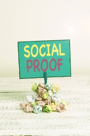 Text sign showing Social Proof. Business photo showcasing informational social influence Psychological Social phenomenon Reminder pile colored crumpled paper clothespin reminder white wooden space Foto de archivo - 131344904