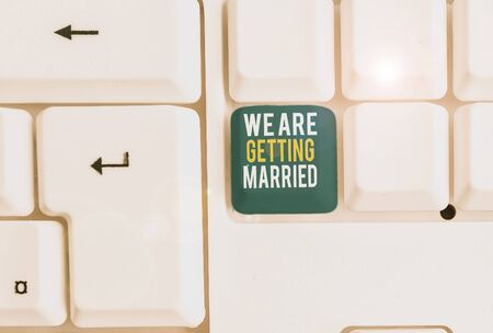 Conceptual hand writing showing We Are Getting Married. Concept meaning Engagement Wedding preparation Loving couple White pc keyboard with note paper above the white background
