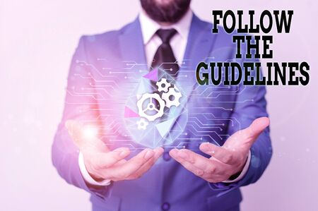 Writing note showing Follow The Guidelines. Business concept for Manual of Style Follow a Specified Rule Accordingly Male human wear formal suit presenting using smart device