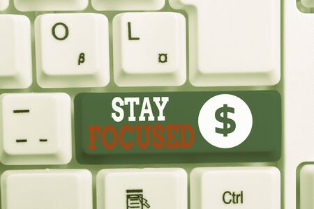 Writing note showing Stay Focused. Business concept for direct time and attention to a limited number of issues White pc keyboard with note paper above the white background Stockfoto