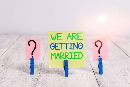 Escritura a mano conceptual mostrando que nos vamos a casar. Concepto Significado compromiso boda preparación pareja amorosa hoja desmoronada con clips colocados sobre la mesa de madera
