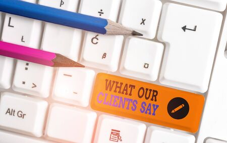 Conceptual hand writing showing What Our Clients Say. Concept meaning testimonials or feedback of aclient about the product White pc keyboard with note paper above the white background Stok Fotoğraf