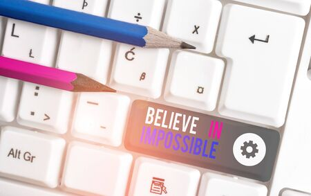 Handwriting text writing Believe In Impossible. Conceptual photo You can do it everything is possible Work hard White pc keyboard with empty note paper above white background key copy space
