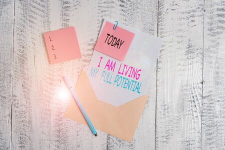 Conceptual hand writing showing I Am Living My Full Potential. Concept meaning Embracing opportunities using skills abilities Envelope blank sheet sticky note ballpoint wooden background