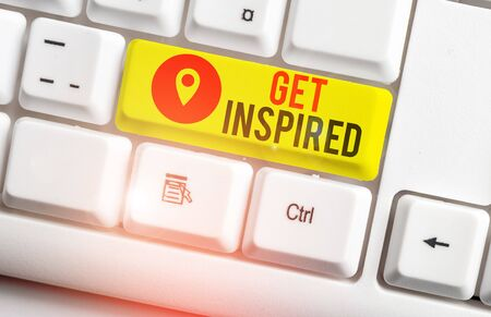 Text sign showing Get Inspired. Business photo showcasing make someone have a particular strong feeling or reaction White pc keyboard with empty note paper above white background key copy space