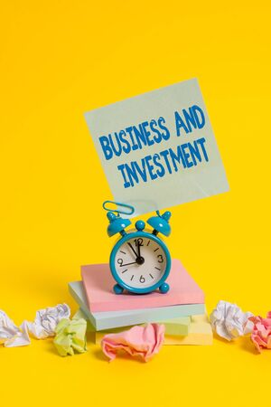 Text sign showing Business And Investment. Business photo showcasing putting your money in field to increase them Alarm clock sticky note paper balls stacked notepads colored background Imagens