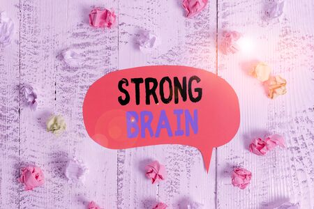 Conceptual hand writing showing Strong Brain. Concept meaning own firm attitudes and opinions and are not easily influenced Colored speech bubble paper balls wooden rustic vintage background