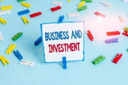 Conceptual hand writing showing Business And Investment. Concept meaning putting your money in field to increase them Colored clothespin papers empty reminder blue floor officepin