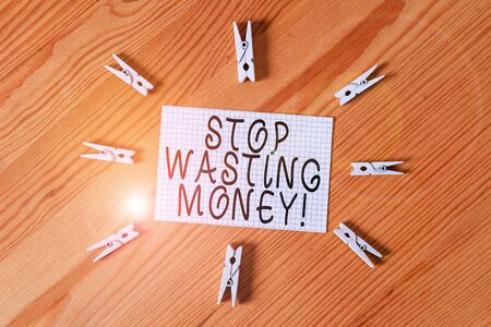 Conceptual hand writing showing Stop Wasting Money. Concept meaning advicing demonstrating or group to start saving and use it wisely Colored crumpled papers wooden floor background clothespin 스톡 콘텐츠