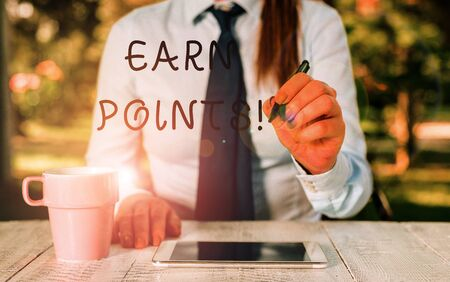 Writing note showing Earn Points. Business concept for collecting scores in order qualify to win big prize Female business person sitting by table and holding mobile phone