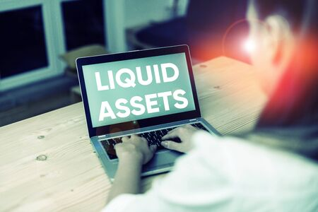 Conceptual hand writing showing Liquid Assets. Concept meaning Cash and Bank Balances Market Liquidity Deferred Stock woman with laptop smartphone and office supplies technology