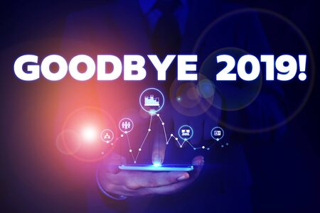 Writing note showing Goodbye 2019. Business concept for express good wishes when parting or at the end of last year Male wear formal suit presenting presentation smart device Stock Photo