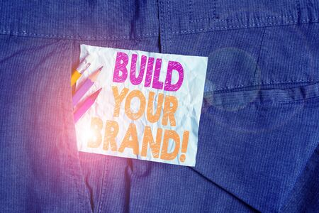 Text sign showing Build Your Brand. Business photo showcasing creates or improves customers knowledge and opinions of product Writing equipment and white note paper inside pocket of man work trousers Stok Fotoğraf