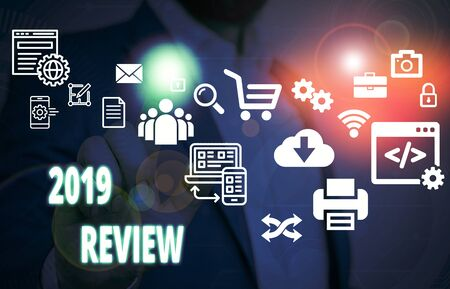Handwriting text 2019 Review. Conceptual photo New trends and prospects in tourism or services for 2019 Male human wear formal work suit presenting presentation using smart device