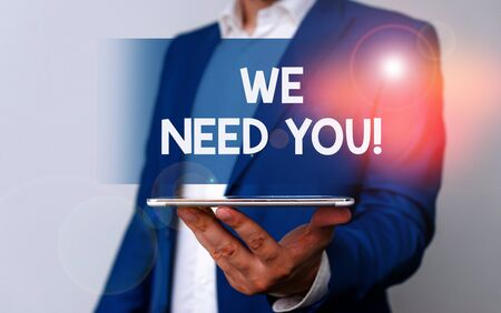 Handwriting text We Need You. Conceptual photo asking someone to work together for certain job or target Man in the blue suite and white shirt holds mobile phone in the hand