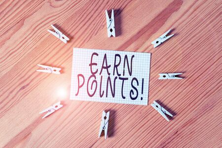 Conceptual hand writing showing Earn Points. Concept meaning collecting scores in order qualify to win big prize Colored crumpled papers wooden floor background clothespin