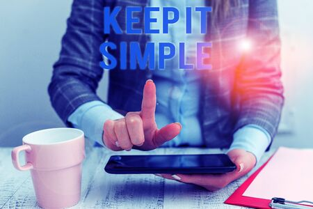 Conceptual hand writing showing Keep It Simple. Concept meaning to make something easy to understand and not in fancy way Business woman sitting with mobile phone and cup of coffee