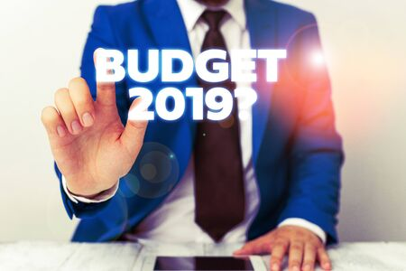 Handwriting text writing Budget 2019 Question. Conceptual photo estimate of income and expenditure for next year Businessman with pointing finger in front of him